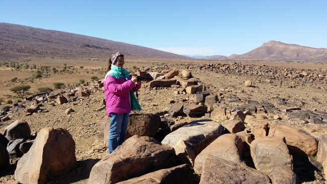 Macarena fotografiando las rocas que contienen los petroglifos