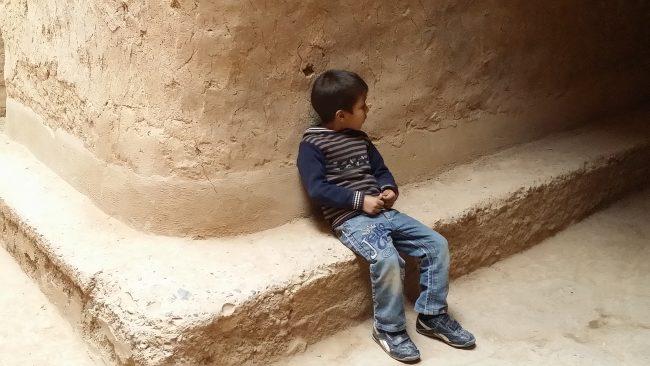 Niño sentado en una calle interior del ksour