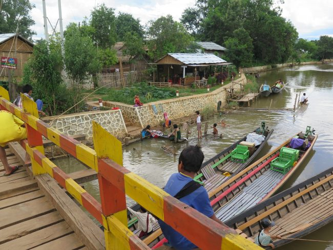 Barcas, niños y mujeres en una aldea birmana